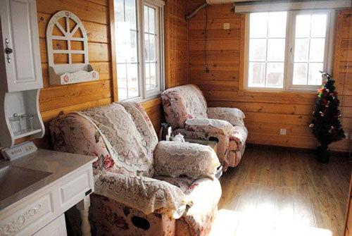 木屋内部是典型的欧式田园风格,松软的沙发上洒满花,象牙白的梳妆台上