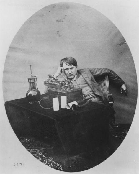爱迪生正在听蜡筒留声机。这种留声机与使用锡箔的留声机类似